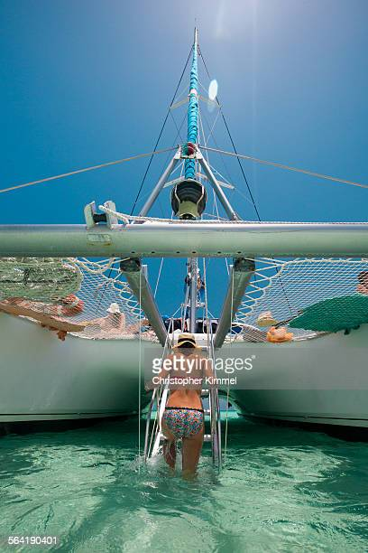 A young woman climbs up ladder to a catamaran boat after swimming in tropical water.