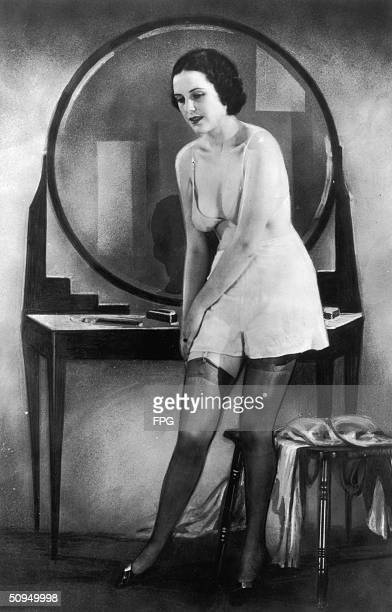 A young woman clips her stockings to a suspender belt circa 1925