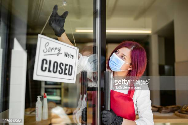 young woman closing her bakery during corona virus - closing stock pictures, royalty-free photos & images