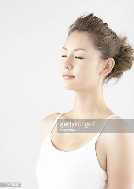 a young woman closing her eyes - 後ろで束ねた髪 ストックフォトと画像