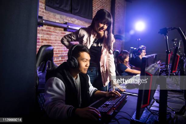 young woman coaching a man playing esports - esports stock pictures, royalty-free photos & images