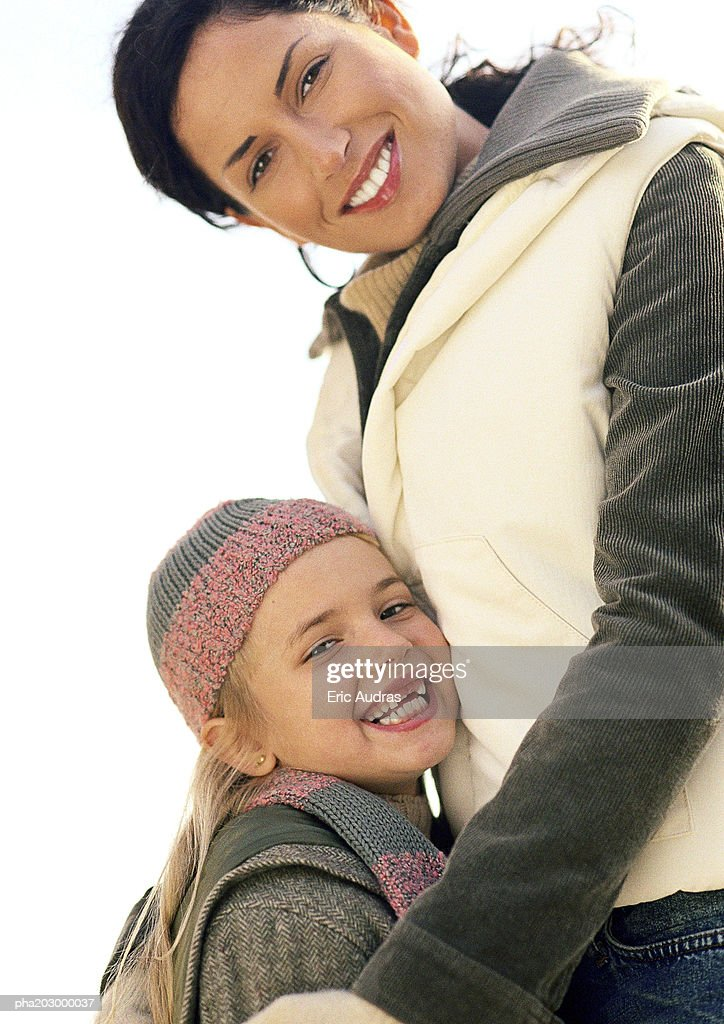 Young woman cocking head, waist up, little girl leaning against her, smiling : Stockfoto