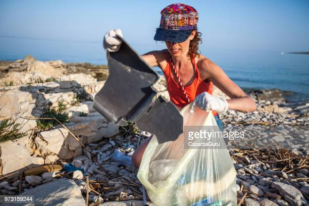 Young Woman Collecting Litter on Seashore