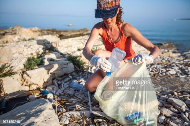 young woman collecting litter on seashore - picking up stock pictures, royalty-free photos & images