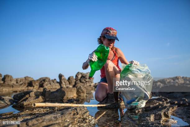 young woman collecting litter on seashore - sollevare foto e immagini stock