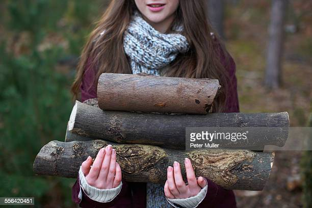 Young woman collecting logs for campfire in forest