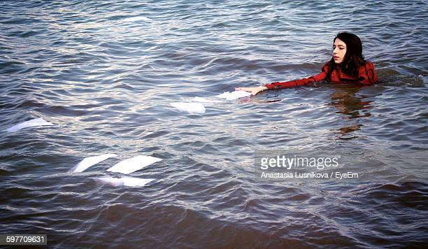 Young Woman Collecting Papers In Sea