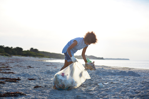 Young woman collecting trash on beach - gettyimageskorea