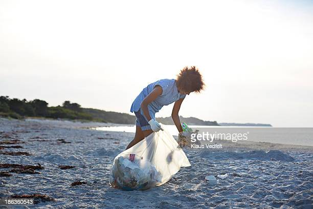 young woman collecting trash on beach - volunteer stock pictures, royalty-free photos & images
