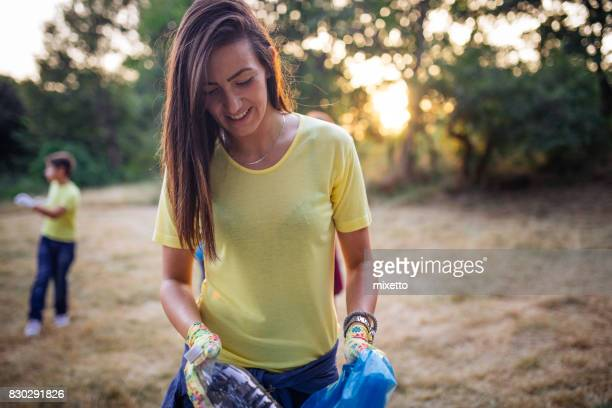 Young woman collects plastic bottles and packs in a bag