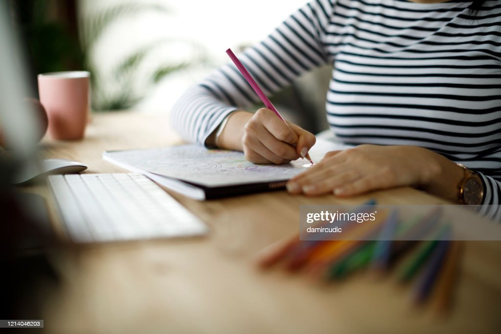 Young woman coloring an adult coloring book : Stock Photo