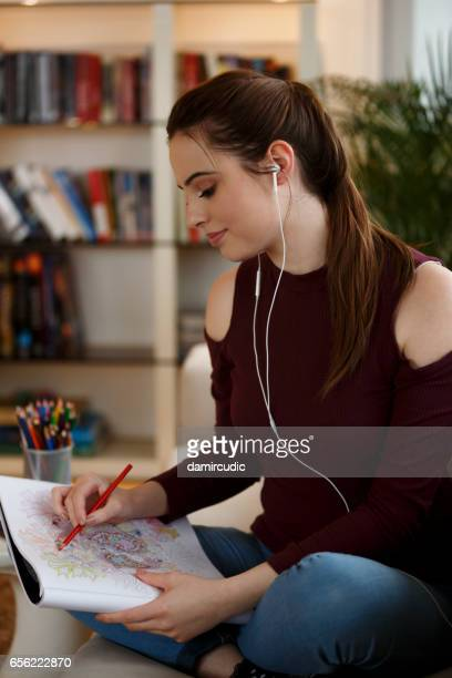 Young woman coloring book and listening music on headphones