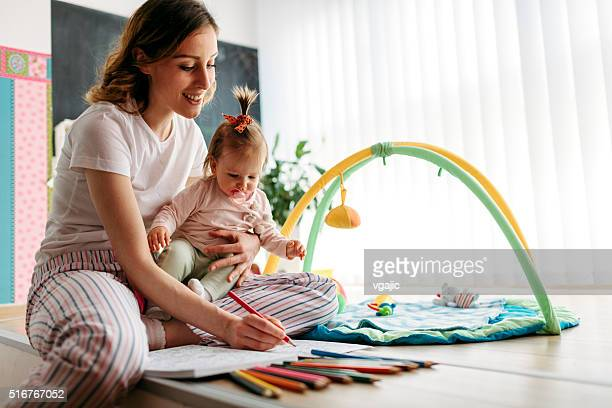 Young Woman Coloring Book With Her Baby