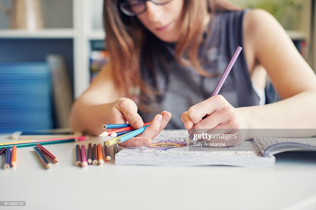 Young woman colouring in an adult colouring book : Stock Photo