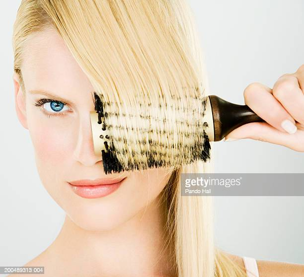 Young woman combing hair, portrait, close-up