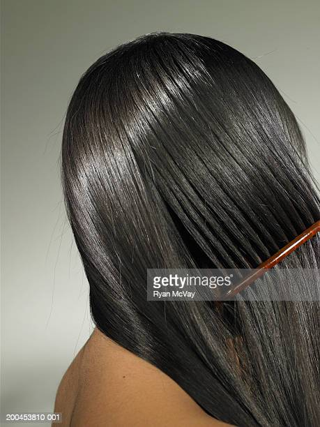 Young woman combing hair, side view