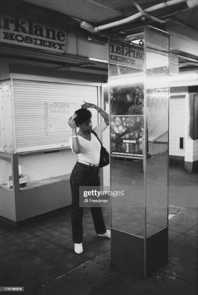 A young woman combs her hair using a pillar as a mirror, Midtown Manhattan, New York City, 1983.