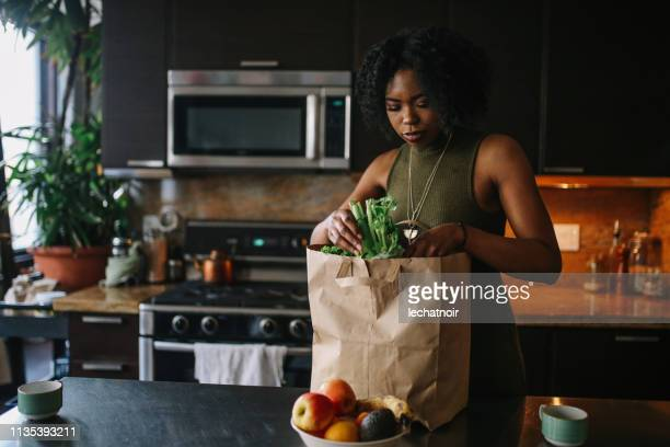 young woman comes home from grocery shopping - grocery bag stock pictures, royalty-free photos & images