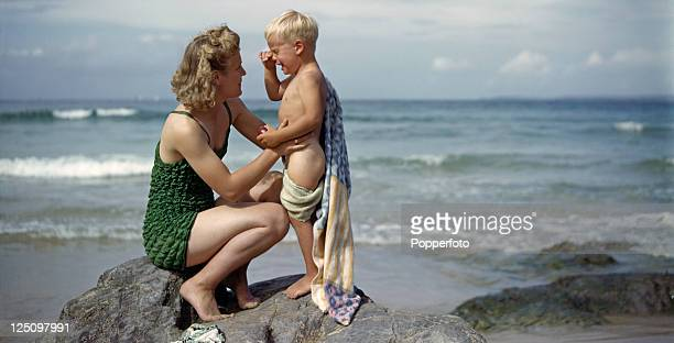 A young woman comforts her little brother who is upset at having to come out of the sea 6th September 1943 The pair are with a group of British war...