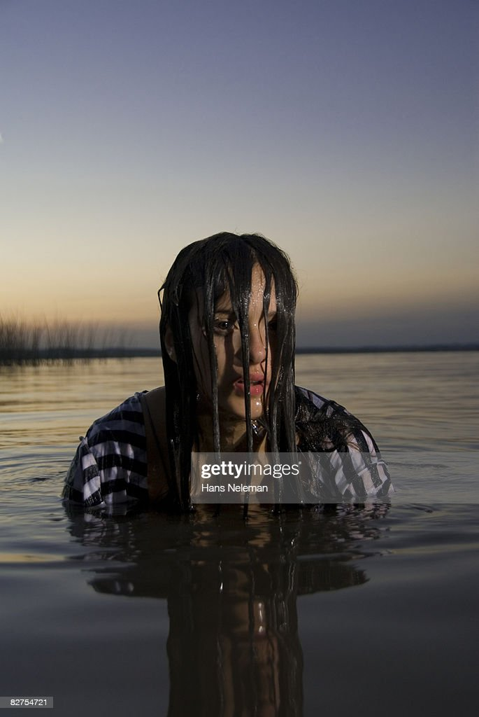 Out Of The Ashes 3: Young Woman Coming Out Of The Water At Dusk Stock Photo
