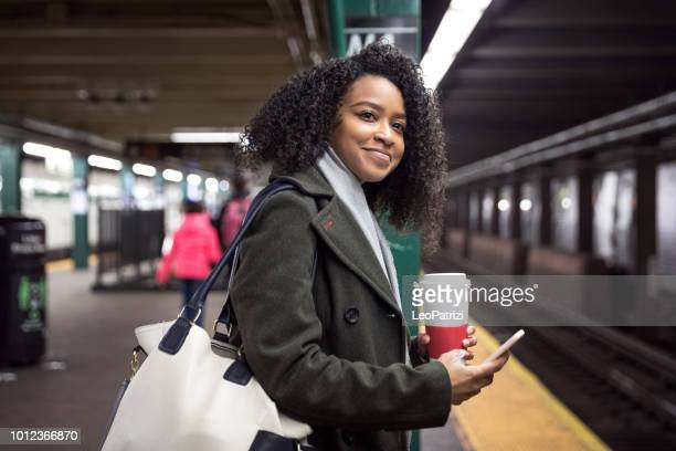 young woman commuter waiting for the subway train in new york - new york city subway stock pictures, royalty-free photos & images