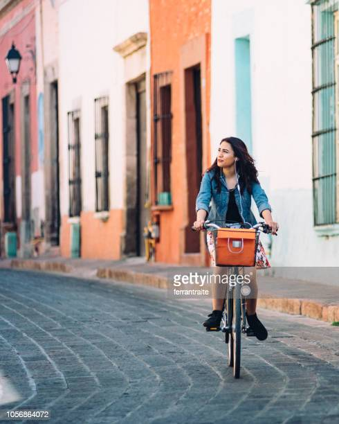 young woman commuting on bicycle - latin america stock pictures, royalty-free photos & images