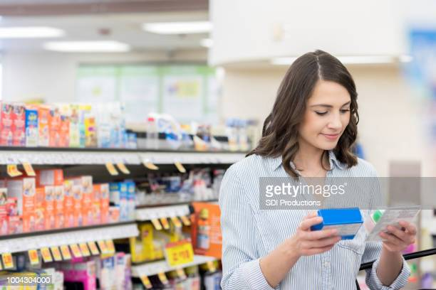 young woman compares medicine labels in pharmacy - pharmacy stock pictures, royalty-free photos & images