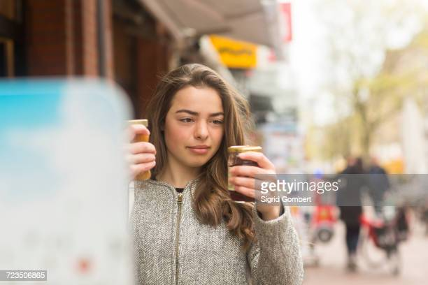 young woman comparing jars of preserve on market stall - sigrid gombert stock pictures, royalty-free photos & images