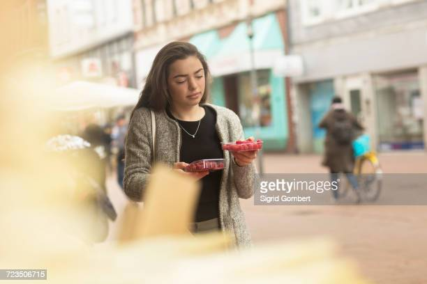 young woman comparing raspberry punnets on market stall - sigrid gombert stock pictures, royalty-free photos & images
