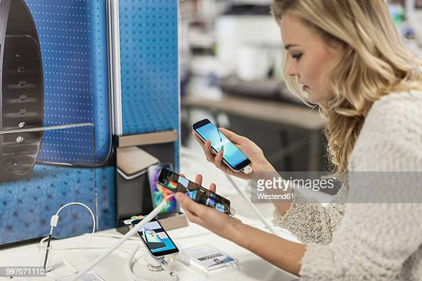 young woman comparing two smartphones in a shop - comparison stock pictures, royalty-free photos & images