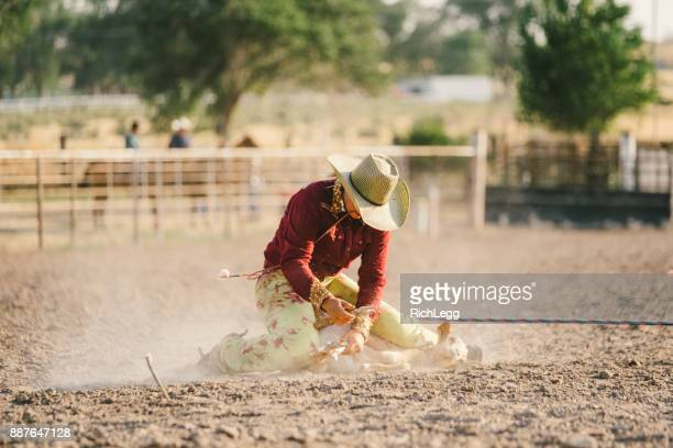 young woman competing in rodeo goat roping - rich_legg stock pictures, royalty-free photos & images