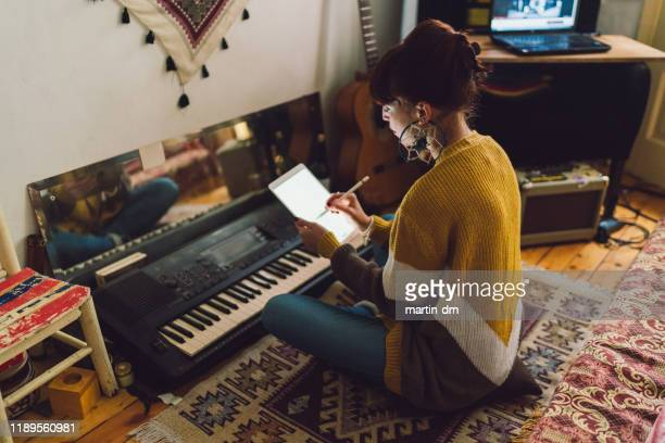 young woman composing new music at home - keyboard player stock pictures, royalty-free photos & images