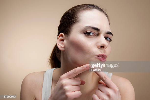 A young woman concentrating as she squeezes a pimple