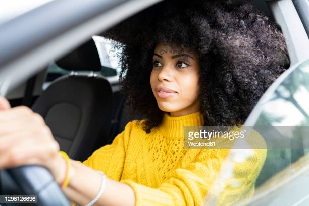 young woman concentrating while driving car - concentration stock pictures, royalty-free photos & images