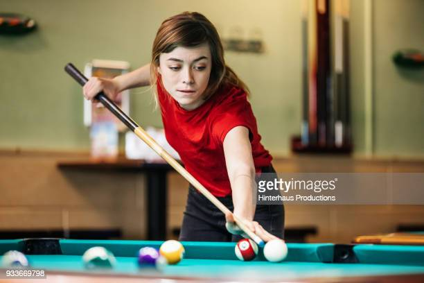 Young Woman Concentrating While Playing Pool