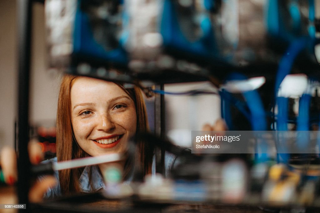 Young woman configures computer for mining : Stock Photo