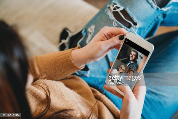 young woman connecting with her family during quarantine - social distancing stock pictures, royalty-free photos & images