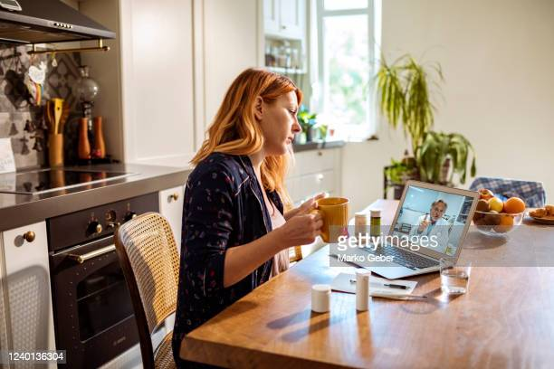 young woman consulting with her doctor over a video call - healthcare stock pictures, royalty-free photos & images