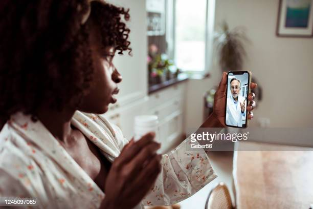 young woman consulting with her doctor - telemedicine stock pictures, royalty-free photos & images