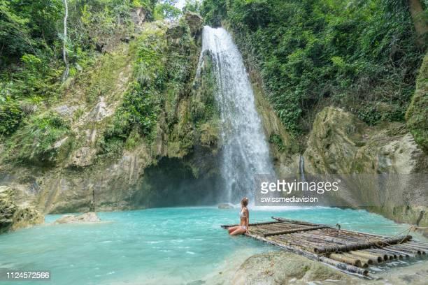 junge frau erwägt schönen wasserfall im tropischen regenwald - cebu stock-fotos und bilder