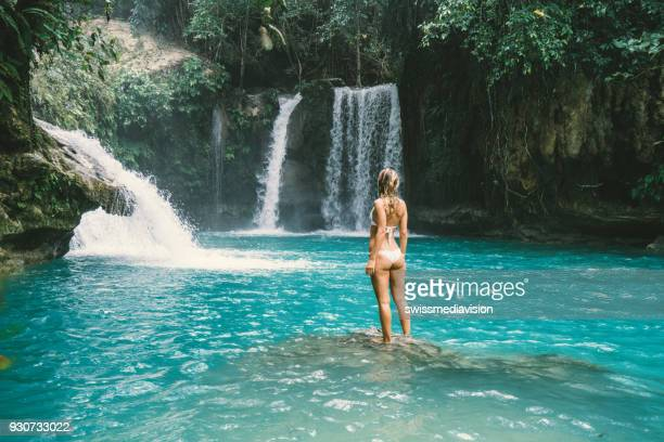 young woman contemplating beautiful waterfall - waterfall stock pictures, royalty-free photos & images