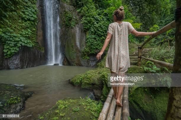 Young woman contemplating beautiful waterfalls in Bali