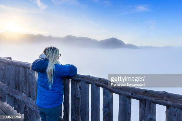 young woman contemplating fog sea from a panoramic point. - italia ストックフォトと画像