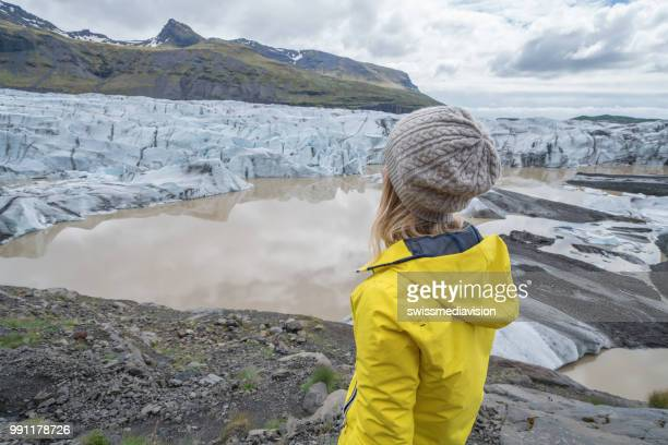 Young woman contemplating glacier lake in Iceland