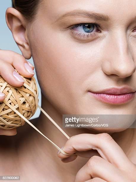 Young woman contemplating her skin elasticity, Studio shot