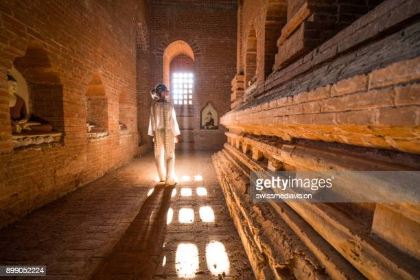 Young woman contemplating inside ancient temple, Myanmar