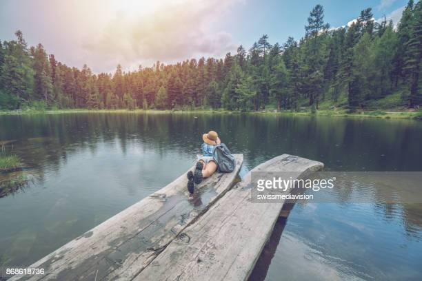 young woman contemplating nature by the lake, switzerland - lake bottom stock photos and pictures