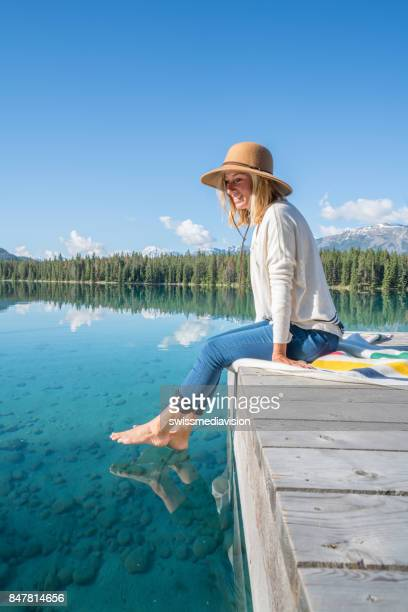 young woman contemplating nature from lake pier - canadian rockies stock pictures, royalty-free photos & images