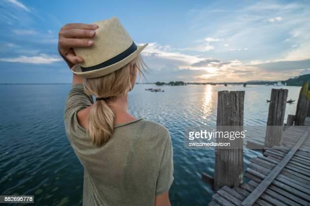 Ubein ブリッジ、ミャンマー、アジアから夕日を見つめる女性