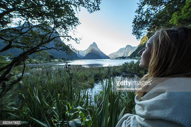 Young woman contemplating the beauty of nature, Milford Sound